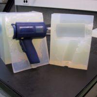 Die Abbildung zeigt eine geöffnete Silikonform mitsamt des darin gegossenen Kunststoffteils