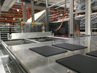 Detailaufnahme Maschine zur Beflammung. Kunststoffteile liegen auf Vorrichtungstisch und fahren unter Brenner, der diese erhitzt